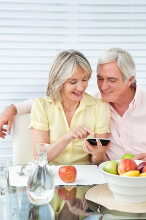 Senior couple using smartphone at breakfast table Stock Photo - 12361507