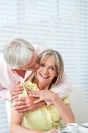 enamorados besandose: Senior hombre besando a su esposa feliz en la mesa del desayuno