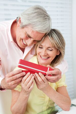 Senior husband offering his happy wife a gift photo