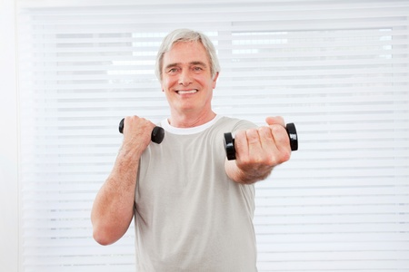 Senior man doing fitness training with dumbbells at gym photo