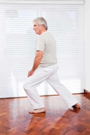 tai chi: Active senior man stretching in gym before fitness training