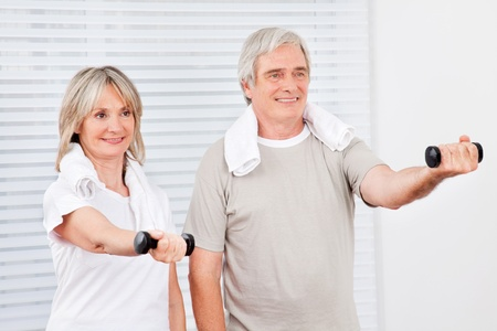 Two happy active seniors doing fitness training in gym with dumbbells photo