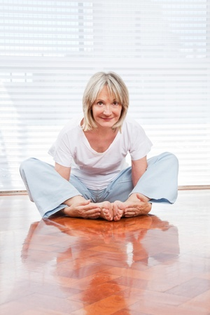 Flexible senior woman in gym doing yoga exercises photo
