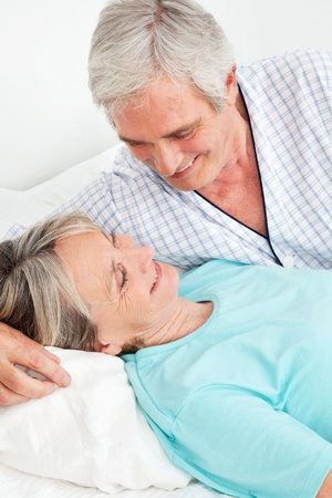 Happy senior couple smiling together in bed in the bedroom Stock Photo - 12361518