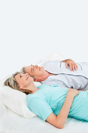 idea comfortable: Pensive happy senior couple laying in bed