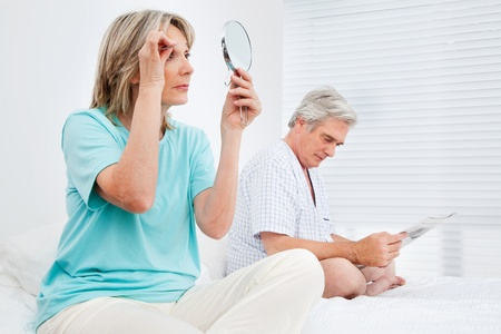 everyday people: Elderly married couple is busy in bedroom before going to bed Stock Photo