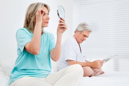 pinzas: Pareja de ancianos casados ??está ocupado en el dormitorio antes de acostarse Foto de archivo