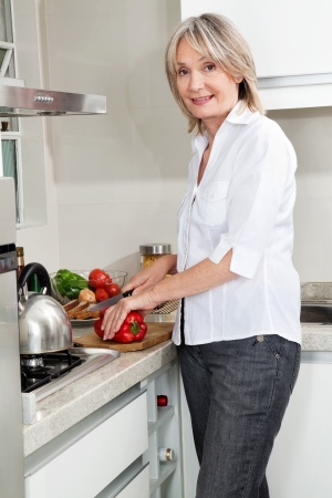 Senior woman cutting pepper for cooking food in kitchen photo