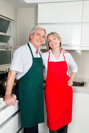 Two happy senior people with aprons in the kitchen photo