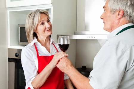 Senior man in kitchen offering his wife red wine photo