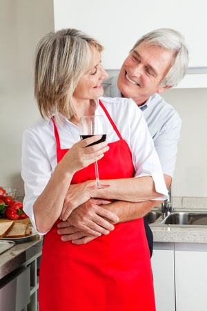 kitchen apron: Happy senior couple in kitchen with glass of red wine