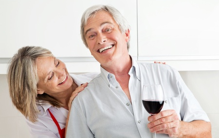 Happy senior couple with glass of red wine photo