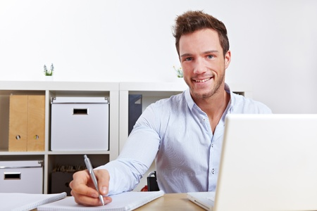 Happy university student learning with laptop and taking notes Stock Photo - 12361583
