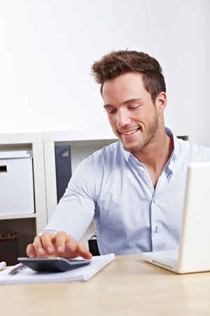 Happy Business man with laptop using calculator photo