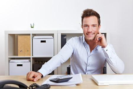 Happy young business man sitting at desk in office Stock Photo - 12361547