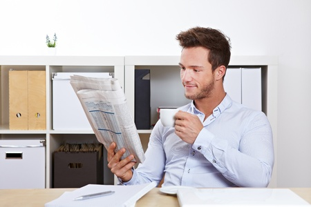 College student at desk reading job market section in newspaper photo