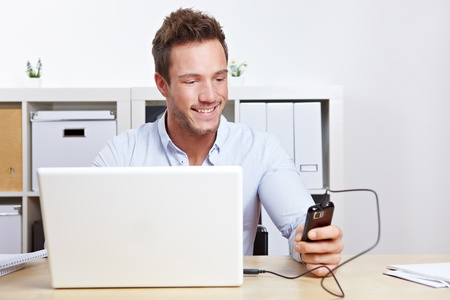 electronically: Young business man connection cell phone to computer in office Stock Photo