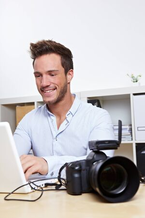 Professional photographer with camera and laptop computer in office photo