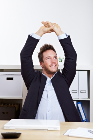 Happy business man in office stretching his back at desk photo