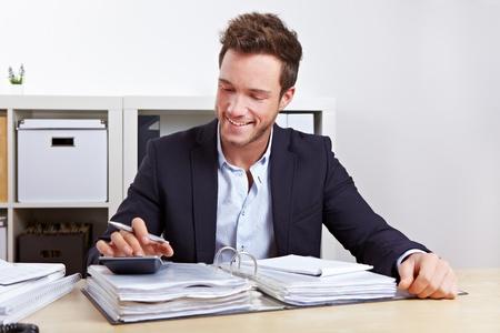 administracion de empresas: El hombre de los ingresos internos haciendo control fiscal con la calculadora en la oficina