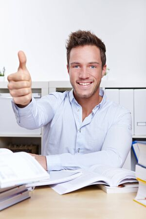 merchant: Successful university student holding thumbs up with books at desk
