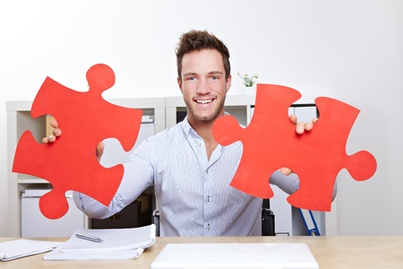 Business man with two oversized red jigsaw puzzle pieces in office photo