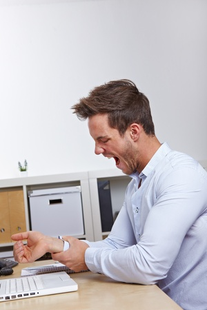 Business man in office holding his aching mouse arm hand photo
