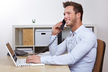 calling: Happy business man with laptop computer in office making phone calls Stock Photo