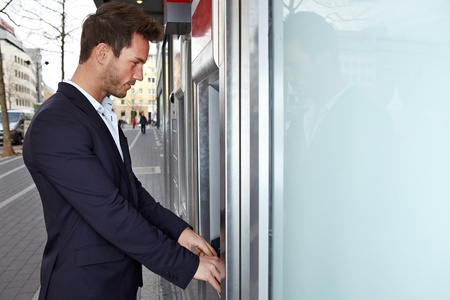 payout: Hombre de negocios en ATM pago en efectivo consiguiendo al aire libre en la ciudad Foto de archivo