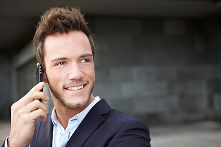 Happy business man making calls with smartphone in city photo