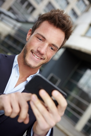 Young business man navigating in urban city with smartphone photo