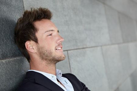 man thinking: Relaxed business man thinking with head leaning on wall Stock Photo