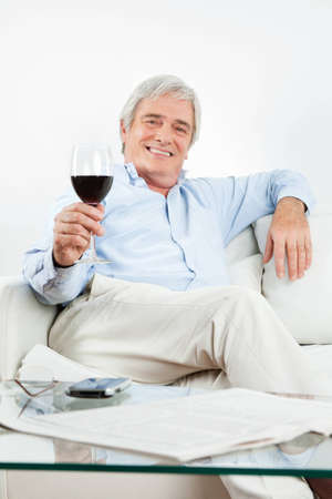Happy senior man toasting with glass of red wine photo