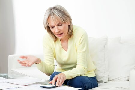 sorting: Frustrated senior woman with paperwork and calculator at home