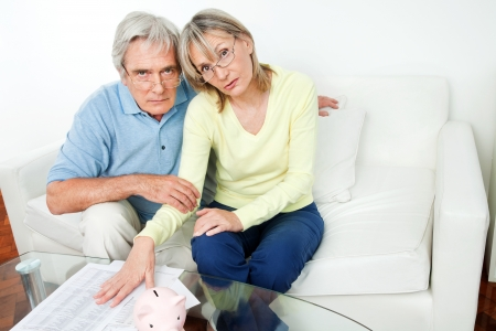 Worried senior couple with bills and piggy bank in living room photo