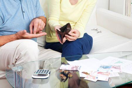 hombre preocupado: Pareja de ancianos contando el dinero del euro en la mesa de sala de estar Foto de archivo