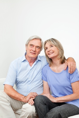 coziness: Smiling senior couple sitting together on couch at home Stock Photo