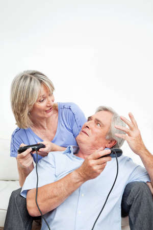 Happy senior couple with game controller playing computer games photo