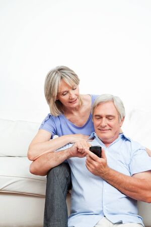 Elderly woman explaining senior man smartphone at home photo
