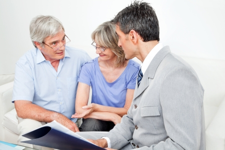 insurance consultant: Investment consultant talking to senior couple at home in living room