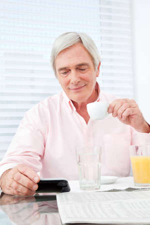 Senior man with coffee looking at smartphone at breakfast table photo