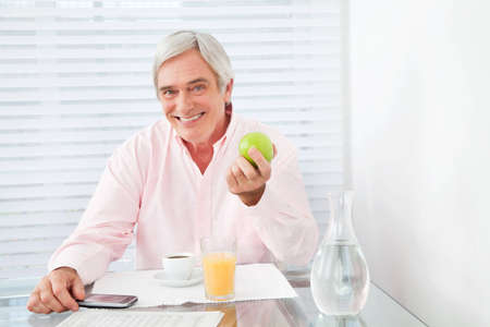 old people eating: Healthy senior man holding apple at breakfast table