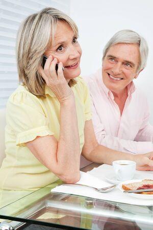 llamando: Superior de la mujer hablando con teléfono celular en la mesa del desayuno
