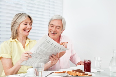 Happy senior couple reading newspaper at breakfast table photo