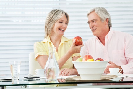 old people eating: Senior woman offering her husband a red apple