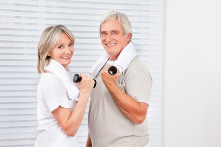 Smiling senior couple doing fitness training with dumbbells in gym photo