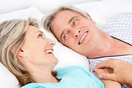 Happy smiling senior couple cuddling in bed Stock Photo - 12361584