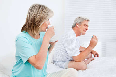 Senior couple relaxing in bedroom with coffee and mp3 player photo