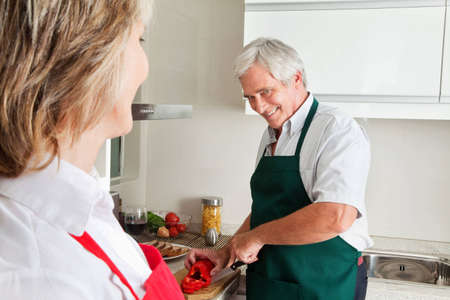 Senior man cutting pepper for cooking in kitchen photo