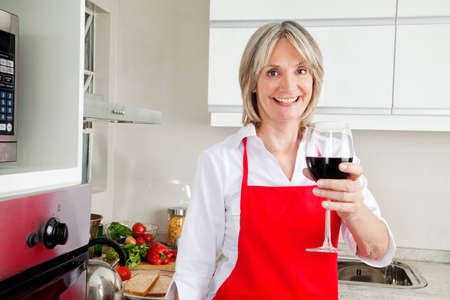 Happy senior woman in kitchen with glass of red wine photo